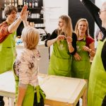 People high fiving in a group wearing aprons
